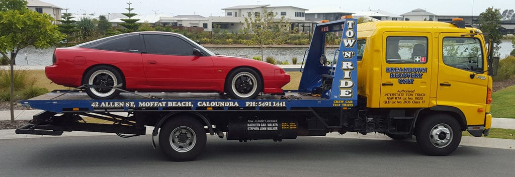 Caloundra towing company tow n ride is towing a red prestige car interstate.