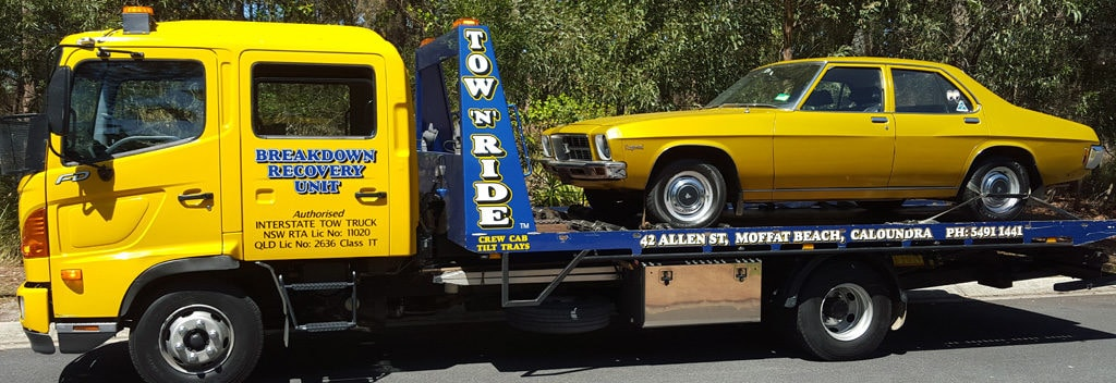 Tilt tray sunshine coast tow truck carrying a gold prestige car.